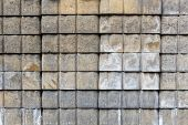 Wall or stack of gray abd tan concrete paver bricks