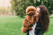 Poodle Dog And His Owner. Adorable Puppy And Young Woman Having Fun In Park, Copy Space poster