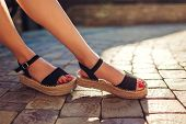 Stylish Woman Wearing Black Summer Shoes With Straw Sole Outdoors. Comfortable Sandals. Beauty Fashi poster