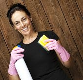portrait of middle aged woman holding spray and scourer against a wooden wall