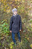 Boy In The Gray Coat Of Autumn, A Little Boy Was Standing In An Autumn Forest In A Gray Coat With A  poster