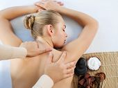 Masseur doing massage on woman body in the spa salon. Girl gets spa procedure. Beauty treatment conc poster