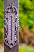 An Old Rusty Thermometer Hanging On A Wooden Pole poster