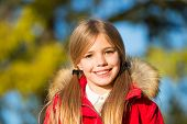 Kid Girl Enjoy Autumn Day. Child Blonde Long Hair Walking In Warm Jacket Outdoor. Girl Charming Smil poster