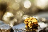 Golden Bar On Raw Coal Nuggets With Soft Focus And Shiny Background poster
