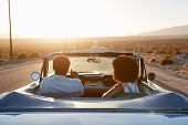 Rear View Of Couple On Road Trip Driving Classic Convertible Car Towards Sunset poster