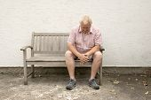 Worried Mature Man Sitting On A Wooden Bench poster
