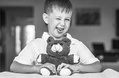 Funny And Naughty Caucasian Child With A Toy Teddy Bear. Kid Showing Tongue. Happy Childhood Concept poster