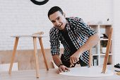 Young Man Assembling Coffee Table And Stools. Furniture Fittings. Engineer With Tool. Young Man At H poster