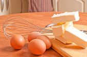 Baking ingredients with eggbeater and cake tin on a wooden kitchen-board