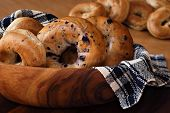 Still life of assorted bagels (blueberry, whole wheat, and cinnamon) in wooden bowl with handwoven c