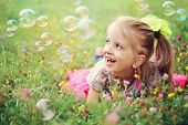 Sweet, happy, smiling six year old girl laying on a grass in a park playing with bubbles and laughin