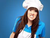 portrait of a female chef clenching on blue background