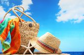 Closeup of summer beach bag and straw hat on sandy beach.