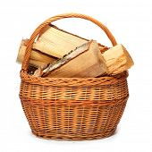 Wicker basket with cut logs fire wood from Silver Birch tree (Betula Pendula). Renewable resource of a energy. Environmental concept.