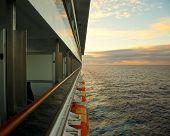 cruise ship seen from outside balcony alongside ship, sunset and horizon