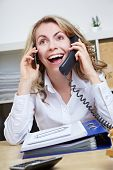 Smiling happy business woman making calls with two phones in her office