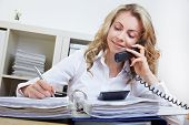 Attractive business woman making a phone call in her office