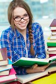 pic of diligent  - Portrait of diligent student looking at camera with open book in hands - JPG