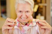 Smiling senior optician holding new glasses in her hands