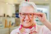 Happy senior woman with new glasses at optician retail store