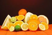 stock photo of pamelo  - Lots ripe citrus on wooden table on dark color background - JPG