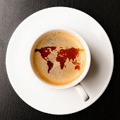 cup of fresh espresso on table, view from above. Earth silhouette is from visibleearth.nasa.gov