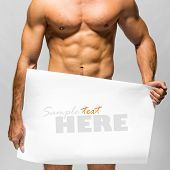 Naked muscular man covering with a banner  (copy space) isolated on white