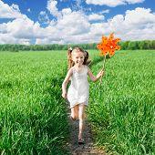 chica de pasto en un día de verano tiene molino de viento en la mano