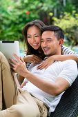 Young Indonesian couple - man and woman - sitting with a tablet computer in the garden