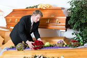 stock photo of coffin  - Undertaker in his store with a display of coffins - JPG