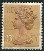 UK-CIRCA 1984: A stamp printed in UK shows image of Elizabeth II is the constitutional monarch of 16 sovereign states known as the Commonwealth realms, in Pale Chestnut, circa 1984.