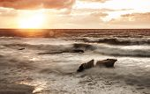Beautiful orange sunset over stormy sea, rocky seashore, tropical beach in the evening, dramatic lan