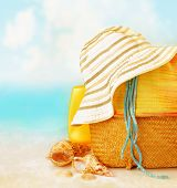 Beach accessories on the sand near sea, skin protection, seashell, hat, bag, day spa, tropical resor