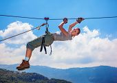 Active happy woman overhanging on tightrope in the mountains on blue sky background, climbing sport,