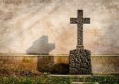Cross on a tombstone on the background of a dark wall