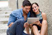 Atractiva pareja con Tablet PC en fondo urbano