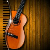 stock photo of bluegrass  - Acoustic brown guitar and piano against a rustic wood background - JPG