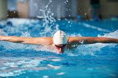stock photo of swimming  - Happy muscular swimmer wearing glasses and cap at swimming pool and represent health and fit concept - JPG