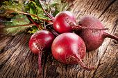 stock photo of root vegetables  - Beet roots on a old wooden table - JPG