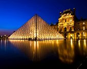 PARIS-APRIL 16: Louvre pyramid shines at dusk during the Summer Exhibition April 16, 2010 in Paris. Louvre is the biggest Museum in Paris displayed over 60,000 square meters of exhibition space.