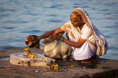 MAHESHWAR, INDIA - APRIL 26: Indian woman performs morning pooja on sacred river Narmada ghats on Ap