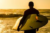 stock photo of atlantic ocean  - A surfer watching the waves at sunset in Portugal - JPG