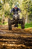 stock photo of motocross  - Quad rider jumping on a forest trail - JPG