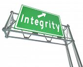 The word Integrity on a green freeway road sign pointing the way to trustworthiness, credibility, virtue and other positive qualities