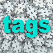 stock photo of hashtag  - The word Tags on a background of hashtag symbols to illustrate message updates by topics to generate news or buzz for a person or event - JPG