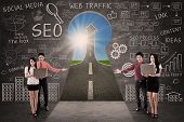 foto of keyholes  - Business team present SEO success road concept through a keyhole - JPG