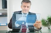 Businessman using futuristic touchscreen to view social network profile in his office