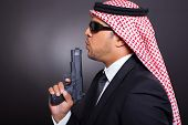 side view of arabian bodyguard with pistol