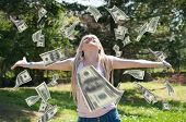 Beautiful blonde with outstretched hands wait for American hundred Dollar bills which fall from the sky, in the park